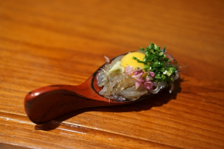 baby sardines served on a spoon with a quail egg yolk